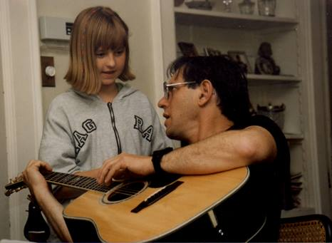 Photo of Leah's father teaching her to play guitar